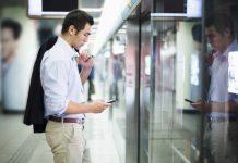 Hombre mirando el móvil antes de subir al metro